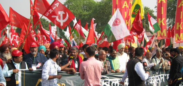 protest showing flags of the All India Kisan Sabha (AIKS)